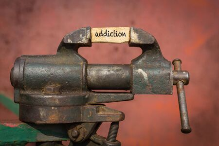 Concept of dealing with problem. Vice grip tool squeezing a plank with the word addiction