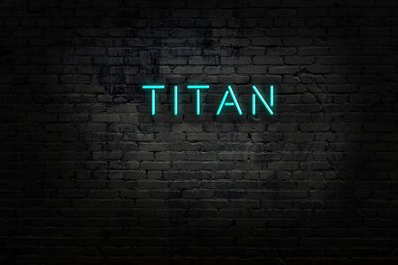 Neon sign with inscription titan against brick wall. Night view