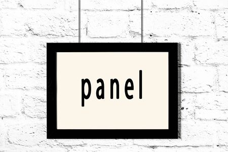 Black wooden frame with inscription panel hanging on white brick wall Stock fotó