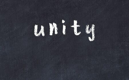 Chalk handwritten inscription unity on black desk 스톡 콘텐츠