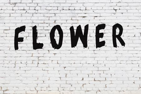 White brick wall with inscription flower handwritten with black paint
