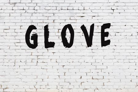 White brick wall with inscription glove handwritten with black paint
