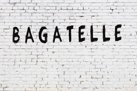 Word bagatelle written with black paint on white brick wall. Imagens