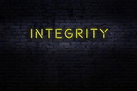 Neon sign on brick wall at night. Inscription integrity 스톡 콘텐츠