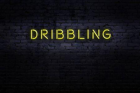 Neon sign on brick wall at night. Inscription dribbling