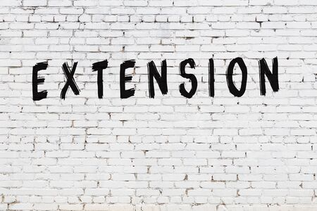 Word extension written with black paint on white brick wall.