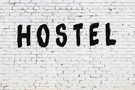 Word hostel written with black paint on white brick wall. Foto de archivo