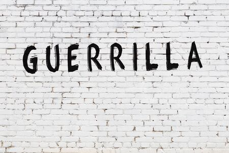White brick wall with inscription guerrilla handwritten with black paint