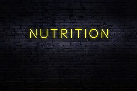 Neon sign with inscription nutrition against brick wall. Night view Foto de archivo