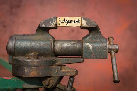 Concept of dealing with problem. Vice grip tool squeezing a plank with the word judgement Imagens