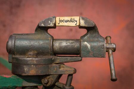 Concept of dealing with problem. Vice grip tool squeezing a plank with the word jocundity