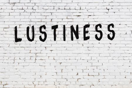 Word lustiness written with black paint on white brick wall.