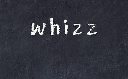 Chalk handwritten inscription whizz on black desk Imagens