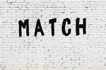 Word match written with black paint on white brick wall.