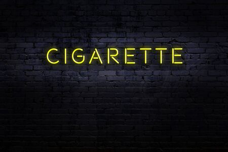 Neon sign with inscription cigarette against brick wall. Night view Stok Fotoğraf