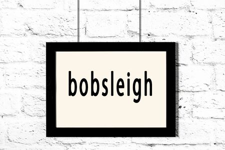 Black wooden frame with inscription bobsleigh hanging on white brick wall