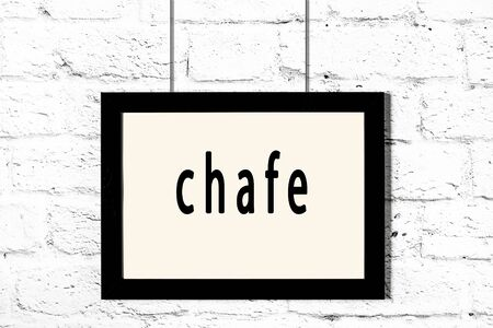 Black wooden frame with inscription chafe hanging on white brick wall
