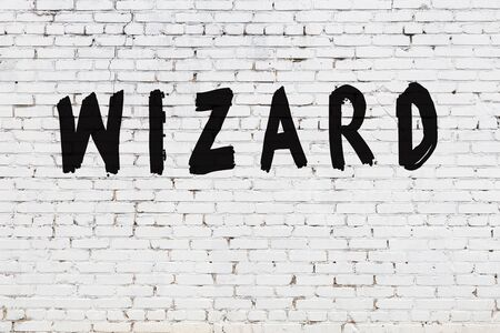 Word wizard written with black paint on white brick wall.