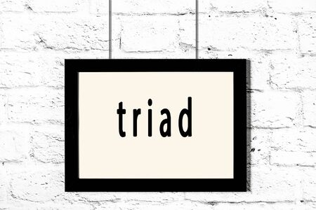 Black wooden frame with inscription triad hanging on white brick wall