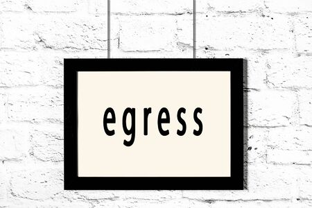 Black wooden frame with inscription egress hanging on white brick wall Foto de archivo