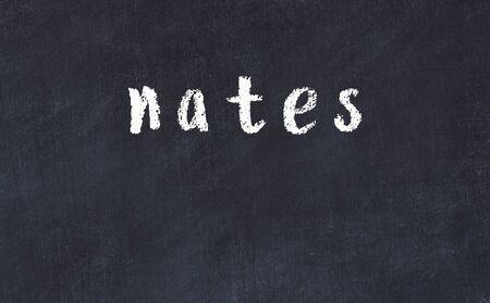 Chalk handwritten inscription nates on black desk