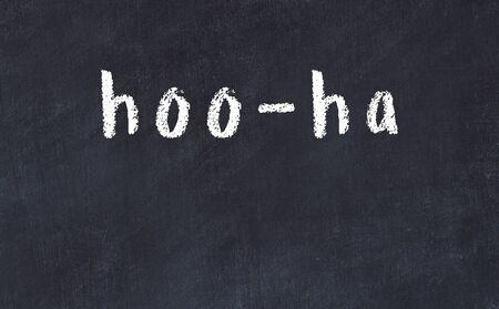 Chalk handwritten inscription hoo-ha on black desk