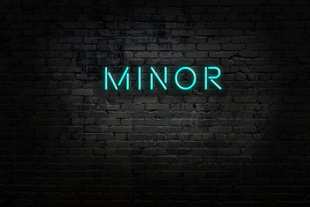 Neon sign with inscription minor against brick wall. Night view