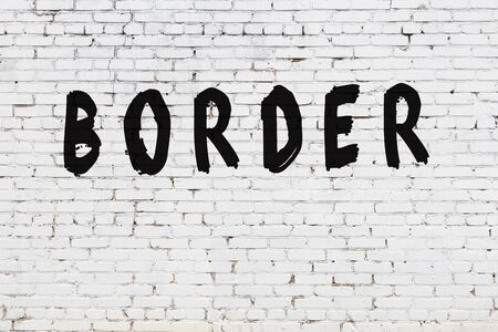 Word border written with black paint on white brick wall.