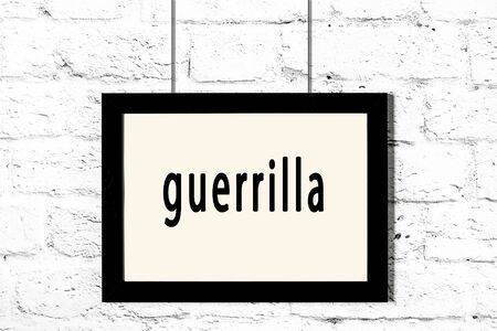 Black wooden frame with inscription guerrilla hanging on white brick wall