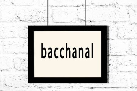 Black wooden frame with inscription bacchanal hanging on white brick wall