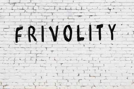 Word frivolity written with black paint on white brick wall.
