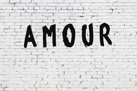Word amour written with black paint on white brick wall. Stock fotó