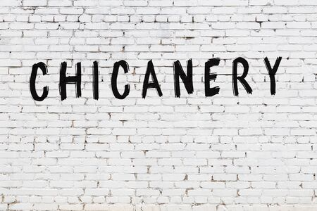 Word chicanery written with black paint on white brick wall. Stock Photo