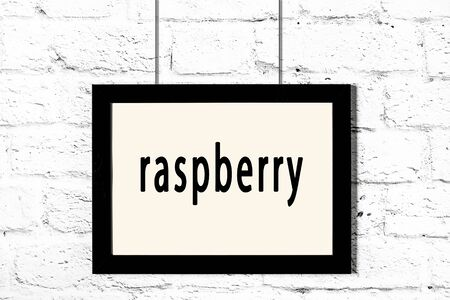 Black wooden frame with inscription raspberry hanging on white brick wall