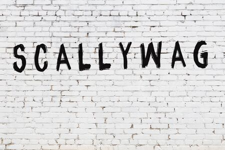Word scallywag written with black paint on white brick wall.