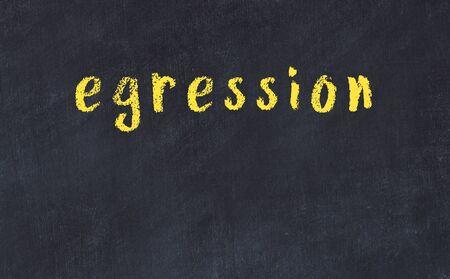Chalk handwritten inscription egression on black desk