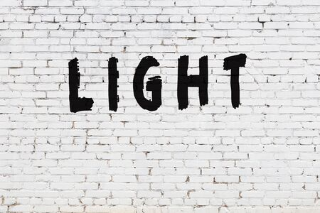 White brick wall with inscription light handwritten with black paint