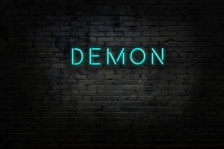 Night view of neon sign on brick wall with inscription demon