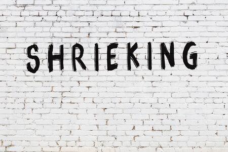 Word shrieking written with black paint on white brick wall.