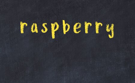 Chalk handwritten inscription raspberry on black desk