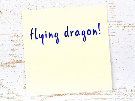 Concept of reminder about flying dragon. Yellow sticky sheet of paper on wooden wall with inscription