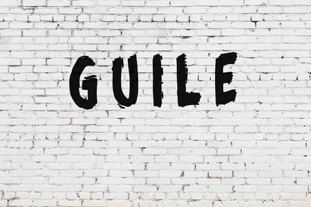 Word guile written with black paint on white brick wall. Stock Photo