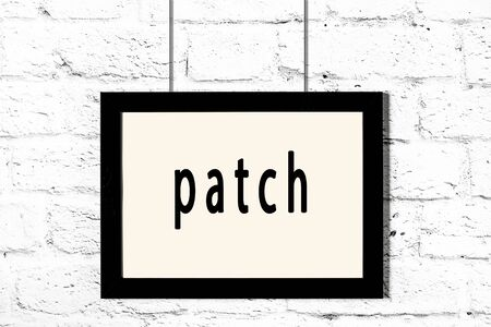 Black wooden frame with inscription patch hanging on white brick wall