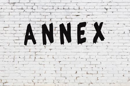 Word annex written with black paint on white brick wall.