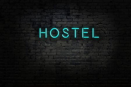 Neon sign with inscription hostel against brick wall. Night view