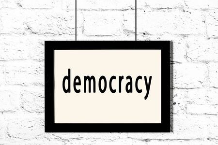Black wooden frame with inscription democracy hanging on white brick wall