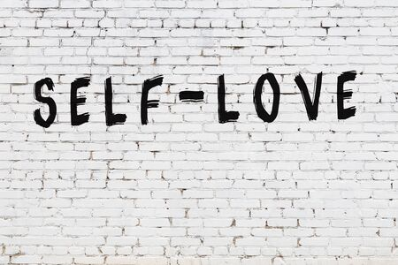 White brick wall with inscription self-love handwritten with black paint