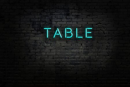 Night view of neon sign on brick wall with inscription table