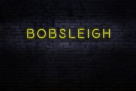 Neon sign on brick wall at night. Inscription bobsleigh Standard-Bild