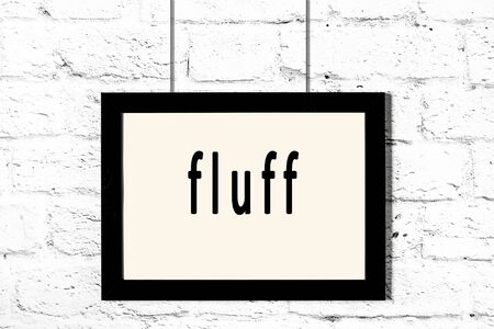 Black wooden frame with inscription fluff hanging on white brick wall Banco de Imagens